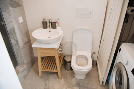 Photo for Modern bathroom with toilet, washbasin and washing machine - Royalty Free Image