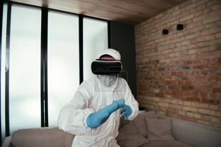 Photo for Man in hazmat suit, medical mask, latex gloves and virtual reality headset gesturing in living room - Royalty Free Image