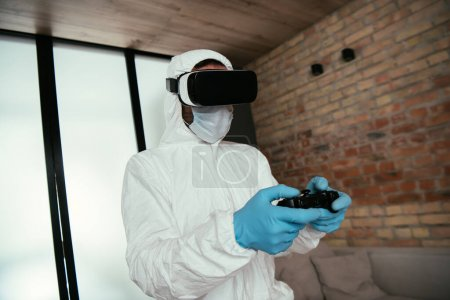 Photo for KYIV, UKRAINE - APRIL 11, 2020: man in hazmat suit, medical mask, latex gloves and virtual reality headset playing video game in living room - Royalty Free Image