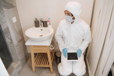 Photo pour Homme en combinaison Hazmat, lunettes, masque médical et gants en latex tenant tablette numérique avec écran blanc dans la salle de bain - image libre de droit