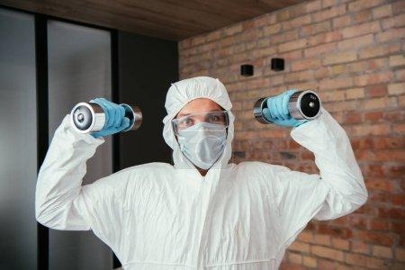 Photo pour Homme sportif en combinaison Hazmat, masque médical et lunettes d'exercice avec haltères dans le salon - image libre de droit