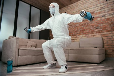 Photo for Sportive man in hazmat suit, medical mask and goggles doing squat exercise with dumbbells near sports bottle and sofa in living room - Royalty Free Image