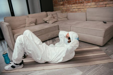 man in hazmat suit, medical mask and goggles exercising near sports bottle in living room