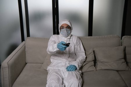 Photo for Man in personal protective equipment holding remote controller while watching movie in living room - Royalty Free Image