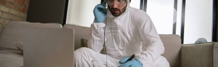 Photo for Panoramic shot of operator in personal protective equipment touching headset and looking at laptop in living room - Royalty Free Image