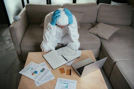 Photo pour Homme en équipement de protection individuelle touchant la tête près d'un ordinateur portable, carnet vierge et cartes de crédit - image libre de droit