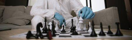 Photo pour Plan panoramique de l'homme en équipement de protection individuelle et masque médical jouant aux échecs - image libre de droit