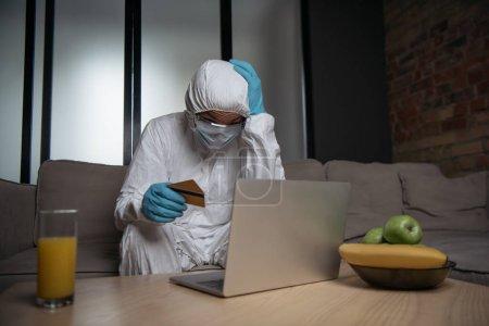 Photo pour Homme en équipement de protection individuelle et masque médical à l'aide d'un ordinateur portable et tenant des cartes de crédit près des fruits et un verre de jus d'orange - image libre de droit