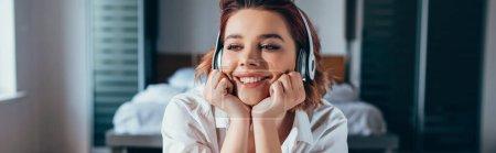 Photo pour Fille souriante écouter de la musique avec écouteurs à la maison pendant la quarantaine, concept panoramique - image libre de droit