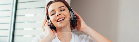 happy girl listening music with headphones at home during quarantine