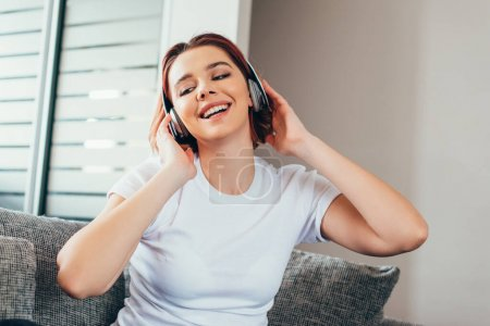 positive girl listening music with headphones while sitting on sofa during quarantine