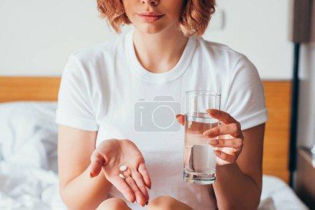 abgeschnittene Ansicht eines Mädchens, das Pille und Glas Wasser zu Hause in der Selbstisolation hält