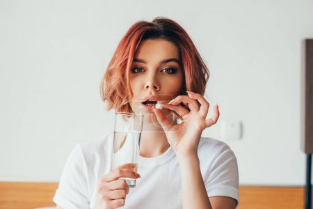 Photo for Attractive girl eating pill and holding glass of water at home on self isolation - Royalty Free Image