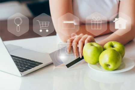 Photo for Cropped view of woman shopping online with laptop and credit cards on kitchen with apples during self isolation with shopping signs - Royalty Free Image