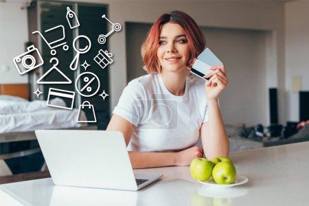 fille positive faisant des achats en ligne avec ordinateur portable et cartes de crédit et des enseignes sur la cuisine avec des pommes pendant l'isolement personnel