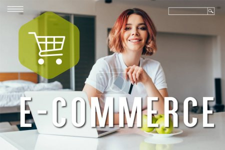 Photo for Smiling girl shopping online with laptop and credit cards on kitchen with apples during self isolation with e-commerce lettering - Royalty Free Image