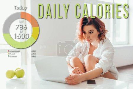attraktives Mädchen mit Kopfhörern mit Laptop in der Küche mit Äpfeln und Smartphone während der Selbstisolierung mit täglichem Kalorienaufdruck