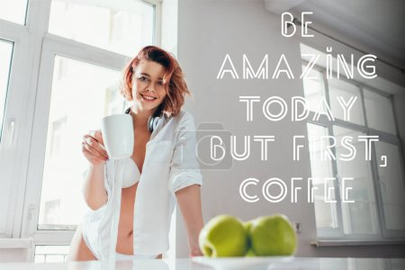 Photo for Beautiful happy girl having coffee for breakfast during self isolation with be amazing today but first, coffee lettering - Royalty Free Image