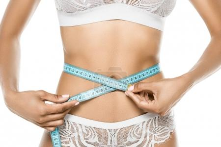 woman measuring waistline with measuring tape