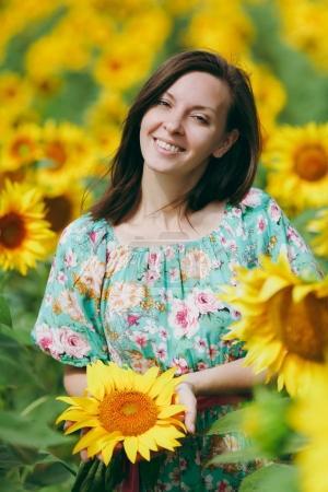Brunette girl in a field of sunflowers