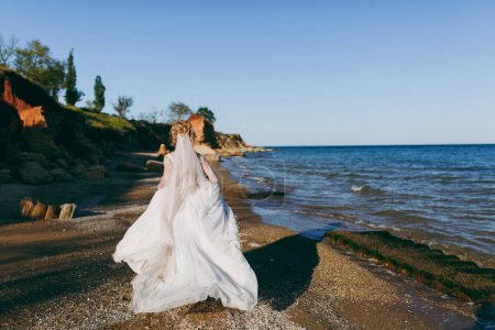 The beautiful blonde bride on a walk by the sea...