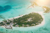 Tropical islands and atolls in Maldives in Indian Ocean from aerial view. Piece of paradise on the Earth. Good choice for vacation. Beautiful top view for wallpaper.