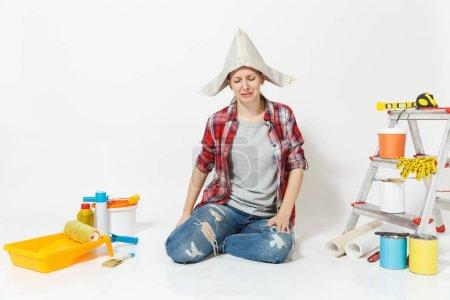 Photo pour Pleurer femme triste dans un chapeau de journal assis sur le sol avec des instruments pour la rénovation appartement pièce isolée sur fond blanc. Papier peint, accessoires pour coller, outils de peinture. Réparation concept de maison - image libre de droit