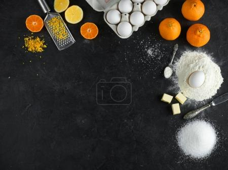 Photo for Ingredients for citrus cake on dark stone background, Top view - Royalty Free Image