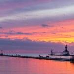 The setting sun paints the sky above Lake Michigan...