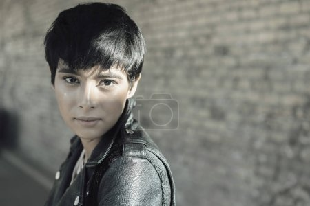 Young woman with short hair sitting wearing leather jacket