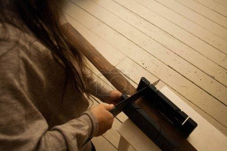 Photo pour Jeune menuisière coupant des jambes de bois à la scie à la maison. Femme effectuant des réparations autour de la maison - image libre de droit