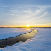 small river through a snowbound fields at the sunset