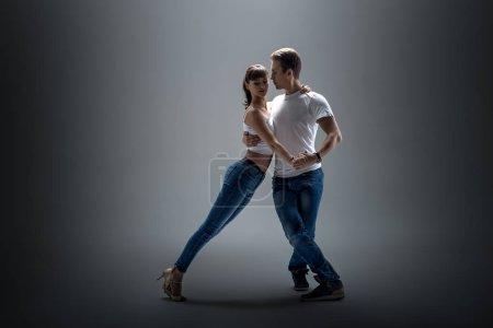 Photo pour Couple beauté dansant danse sociale (kizomba ou bachata ou semba ou taraxia), sur fond gris - image libre de droit