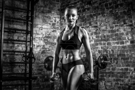 Photo for Young fitness woman execute exercise with dumbbells in gym on brick background, horizontal black-and-white photo - Royalty Free Image