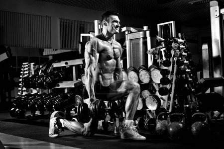 very power athletic guy , execute exercise with  dumbbells, in g