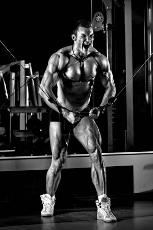 very power athletic guy bodybuilder, execute exercise with gym c
