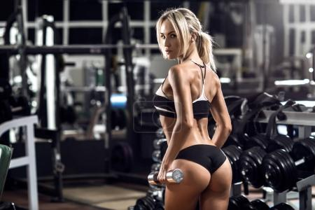 Photo for Young fitness woman execute exercise in gym, horizontal photo - Royalty Free Image