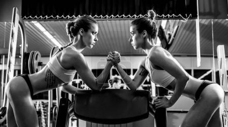 Photo for Two young fitness woman, arm wrestling in gym, horizontal black-and-white photo - Royalty Free Image