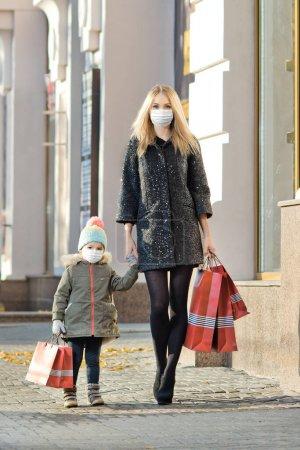 Photo pour Femme et petit enfant en masque médical avec sac à provisions rouge, marchant dans la rue. Concept covid-19 pandémie de coronavirus - image libre de droit