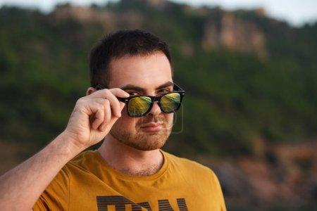 Photo pour Un homme attractif portant des lunettes jaunes se détend sur la plage au coucher du soleil. - image libre de droit