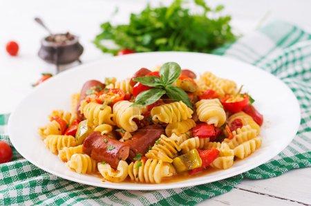 Photo pour Pâtes à la sauce tomate avec des saucisses, tomates, basilic vert décoré en plaque blanche sur un fond en bois et de la serviette. - image libre de droit