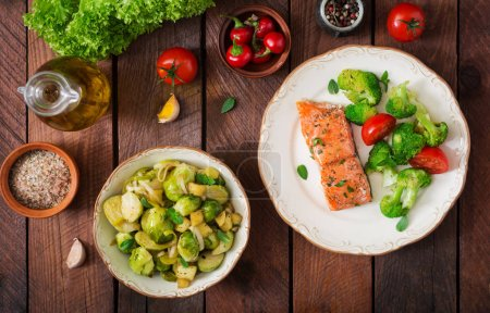 Baked salmon in plate and bowl with sprouts