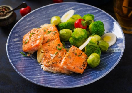 Baked salmon with broccoli in blue plate