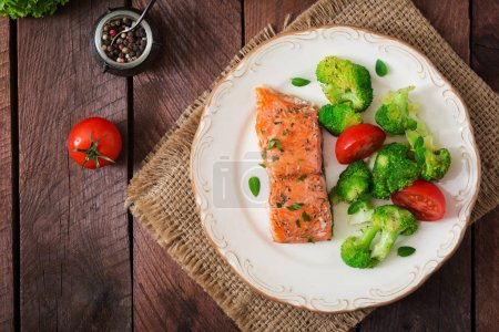 Baked salmon garnished with broccoli and tomatoes