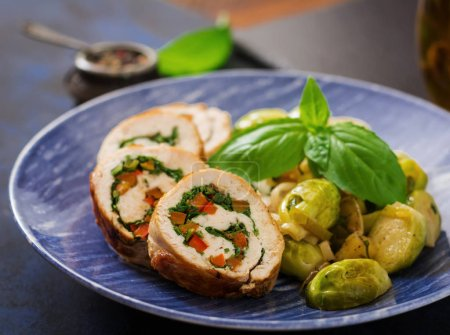 Chicken rolls with greens on blue plate