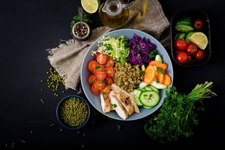 Photo for Healthy salad with chicken, tomatoes, cucumbers, lettuce, carrots, celery, red cabbages and mung beans on dark background. Proper nutrition. Dietary menu. Flat lay. Top view - Royalty Free Image