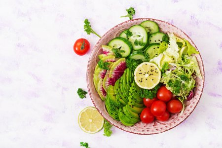 Photo for Diet menu. Healthy lifestyle. Vegan salad of fresh vegetables - tomatoes, cucumber, watermelon radishes and avocado on bowl. Flat lay. Top view - Royalty Free Image