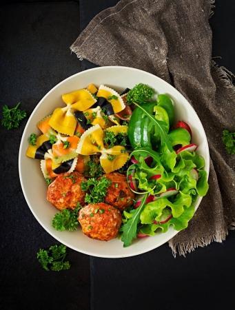 Photo pour Vue de dessus des pâtes aux boulettes de poulet cuit au four avec sauce et salade dans un bol sur fond sombre. - image libre de droit