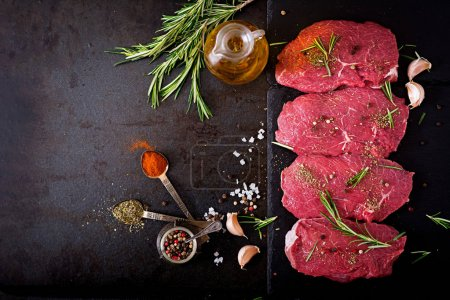 Photo for Raw beef steaks with spices and rosemary on cutting board - Royalty Free Image