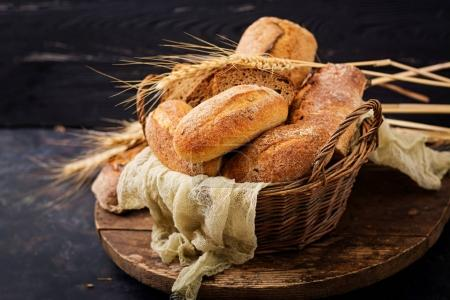 Photo for Assortment of baked bread in basket on wooden background - Royalty Free Image